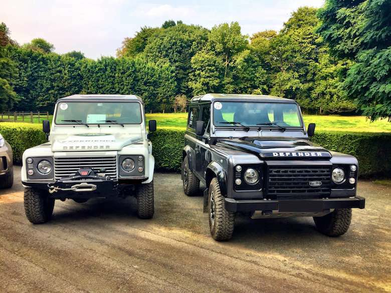 Two Land Rover defenders against a green background