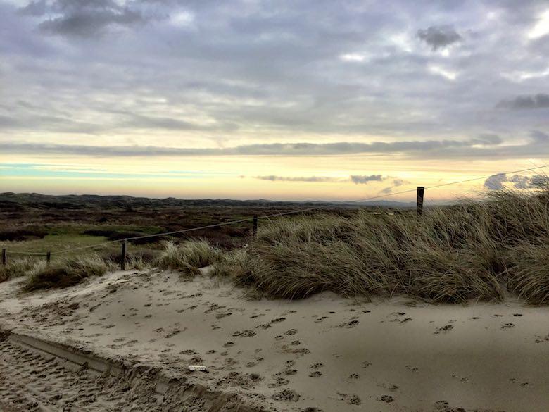 De duinen onder een openbrekende hemel tijdens een najaarsuitje op Texel met het gezin