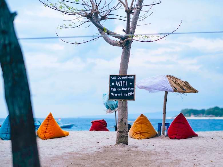 Beach with bean bags and a no wifi sign in the context to protect your online identity while traveling