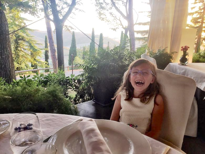 A girl laughing out loud in a fancy restaurant at the Palazzo di Varignana Resort & Spa, one of out favorite family-friendly luxury hotels