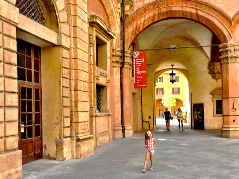 A little girl exploring the courtyard of the Palazzo d'Accursio, housing the City Art Collection and Town Hall, in vibrant Bologna