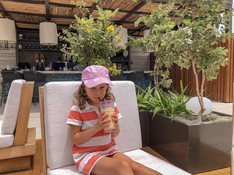 Little girl enjoying a smoothie at the Swell pool bar at the Alohilani Resort in Waikiki Beach