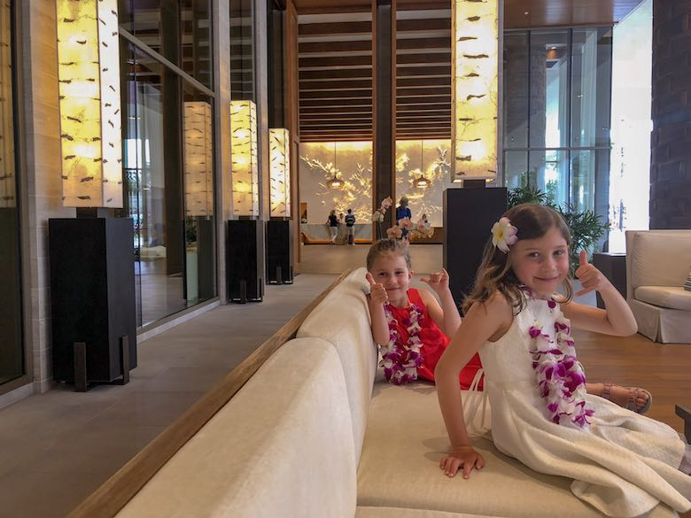 Two little sisters wearing a lei while sitting in the sofa at the entrance of the Alohilani Resort in Waikiki Beach
