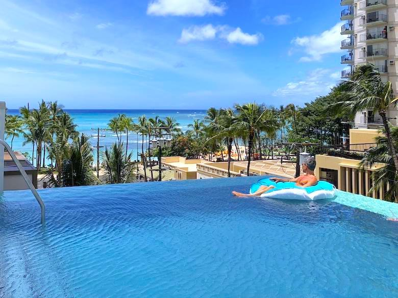 CosmopoliDad enjoying the view from the infinity pool at the Alohilani Resort in Waikiki Beach