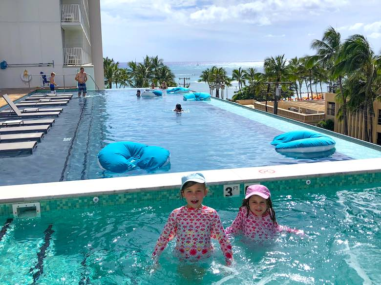 Two little girls enjoying the jacuzzi pool at Alohilani Resort Waikiki Beach, a family-friendly luxury resort in Honolulu