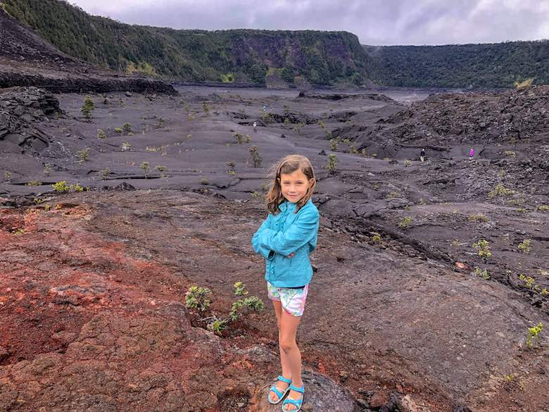 Little girl proudly posing at the crater during a hike of the Kilauea Iki Trail in Hawaii Volcanoes National Park on Hawaii Big Island