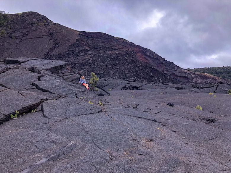 Little girl sitting on the warm crater floor during a hike of the Kilauea Iki trail in Hawaii Volcanoes National Park on Big Island Hawaii
