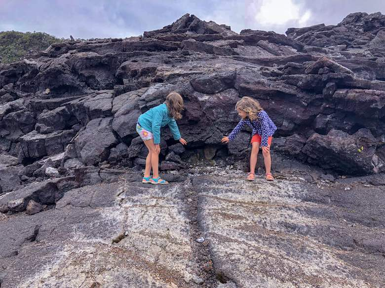 Two little girls feeling the steam from a vent in the Kilauea Iki crater on Hawaii Big Island