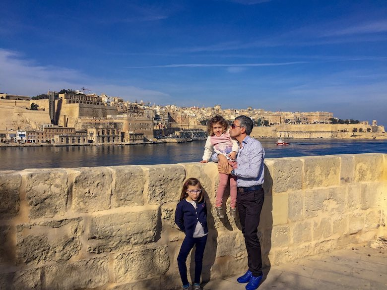 Dad and his 2 little girls with in the background a view over the Grand Harbour and Valletta