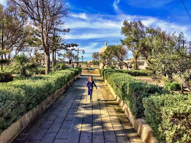 Little girl running down the path of Gardjola Gardens in Senglea or Isla, one of Three Cities Malta