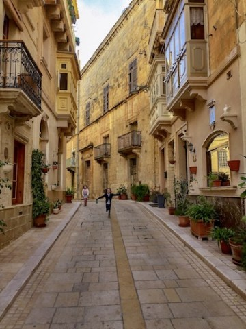 Two little girls running down a narrow street in Vittoriosa or Birgu, one of the Three Cities in Malta