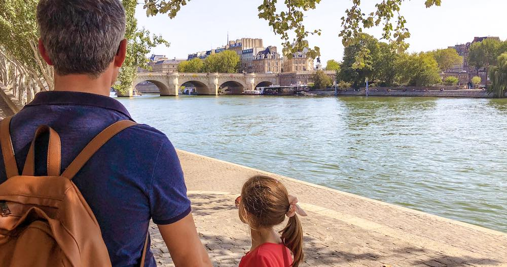 Father and daughter taking a stroll along the Seine during their four days in Paris