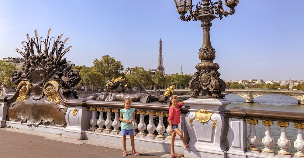 Two sisters posing at Pont Alexandre III, a landmark that cannot be missed during a 4-day Paris itinerary because of the Eiffel Tower views