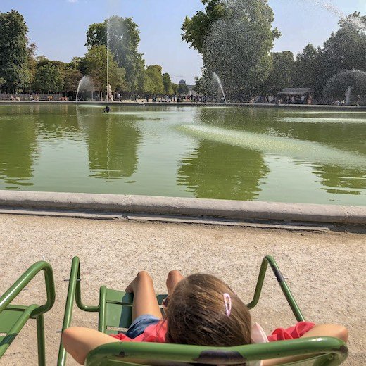 Little girl lounging at Jardin des Tuileries during an exhausting 4 days in Paris
