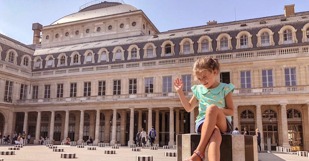 Little girl sitting on a pillar at the Palais Royal, a must-see Paris attraction