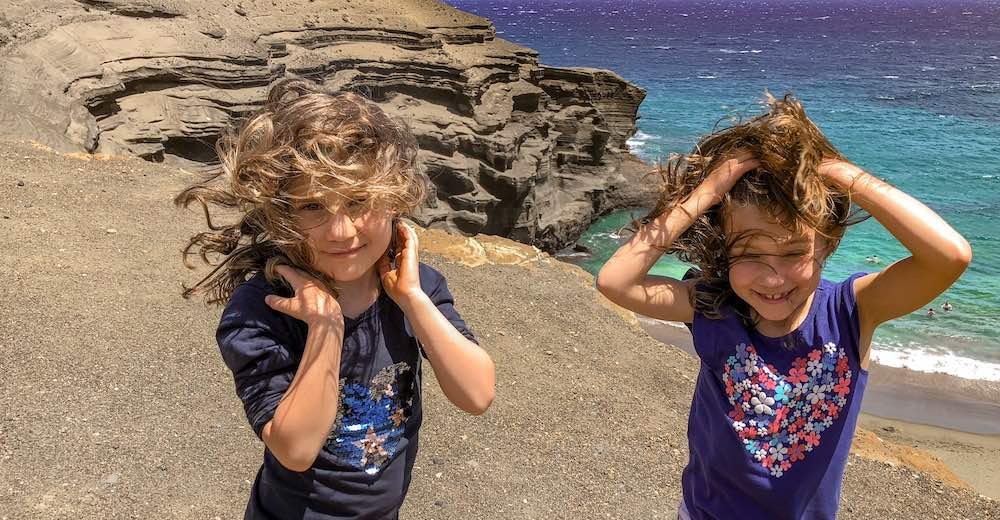 Wind and sand hitting these girls in the face at Papakolea green sand beach on Hawaii Big Island
