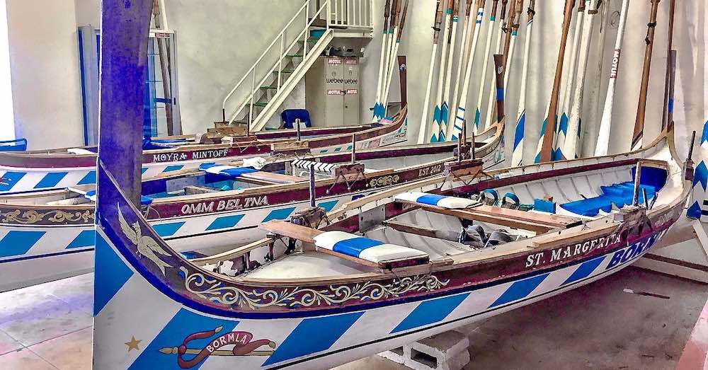 The club house of the Bormla regatta race crew, with the blue and white striped boars awaiting the next race