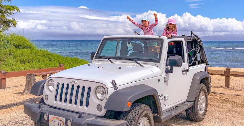 Two girls cheering from a convertible jeep, a great way to go island hopping in Hawaii