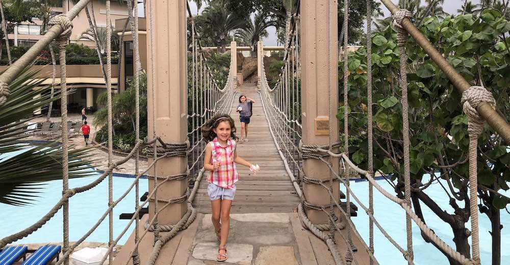 Little girl running towards the camera on a suspension bridge at Hilton Waikoloa Village, the best place to stay on Big Island if you like a theme park atmosphere in your hotel