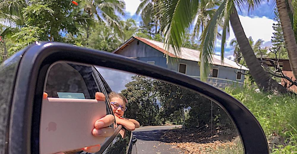 Little girl in the back seat as seen from the rear view mirror during a road trip through Hawaii Big Island