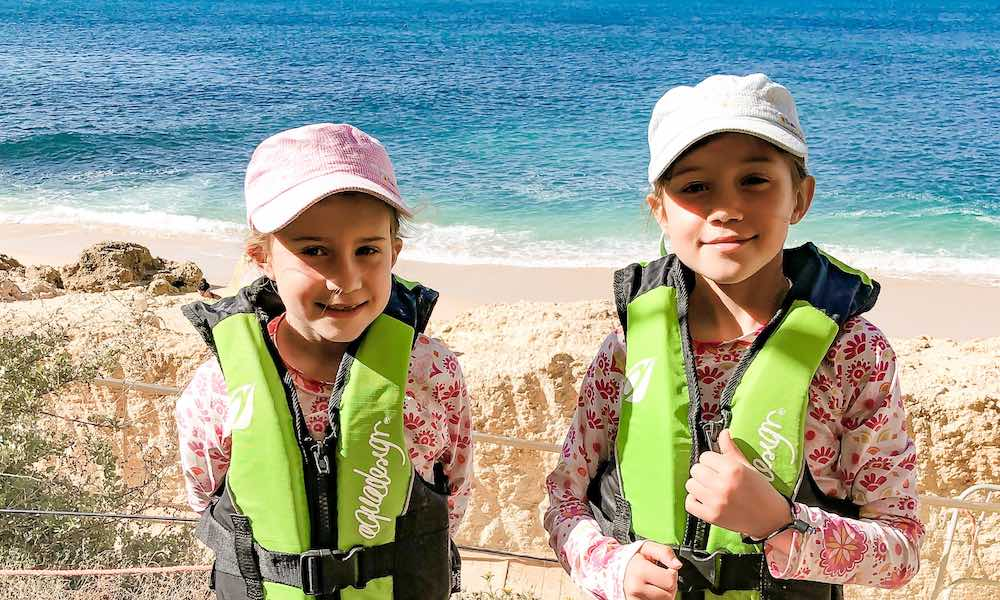 Two girls wearing safety vests and a hat, ready to kayak the Algarve coastline