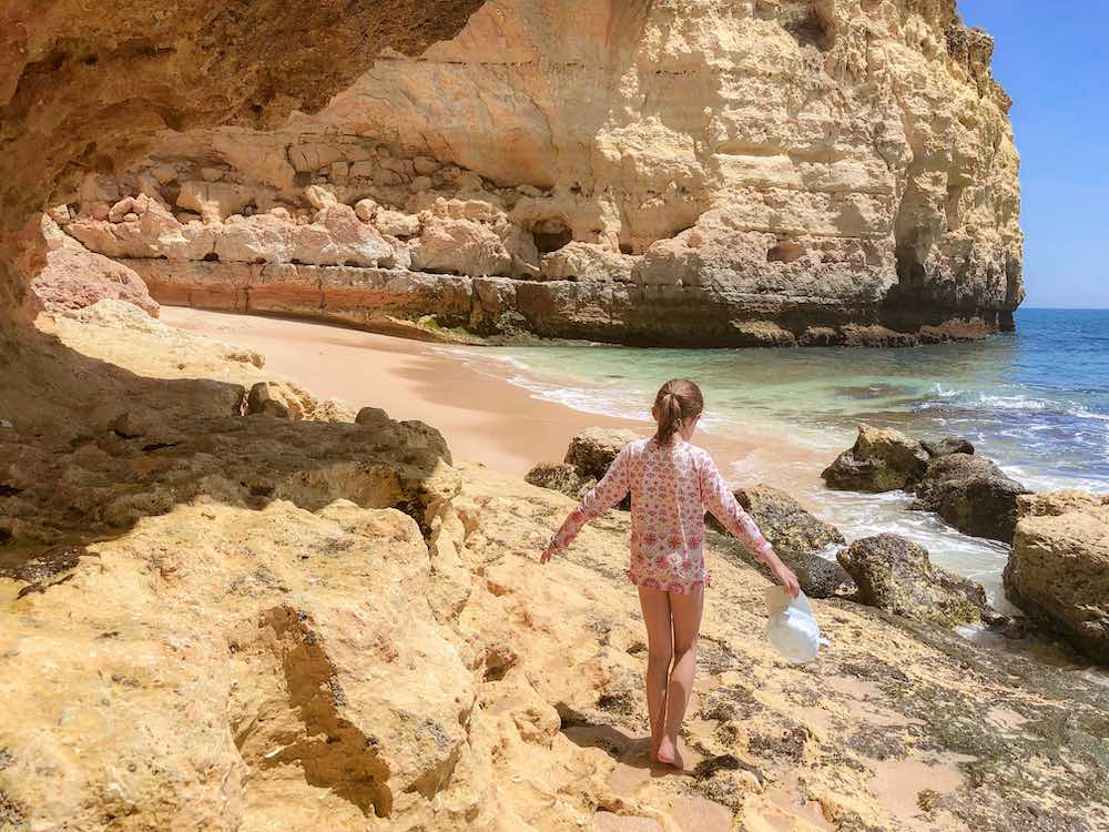 Little girl climbing the limestone rocks at Praia do Vale de Centeanes, one of the Algarve beaches in Portugal