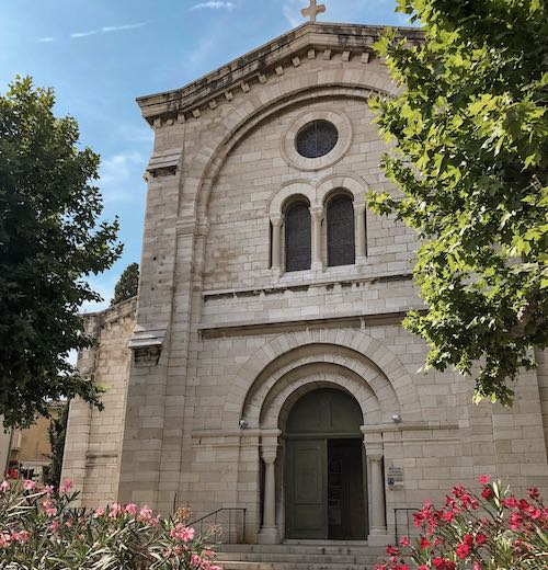 Beautiful church facade from behind the oleander pots at Cassis Provence