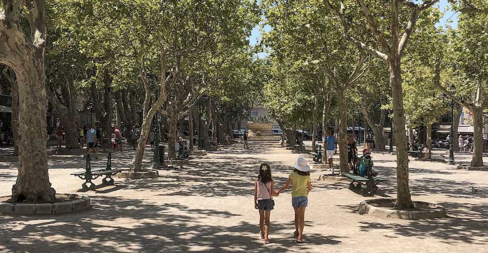 Two sisters walking hand in hand at the Places des Lices in St Tropez France