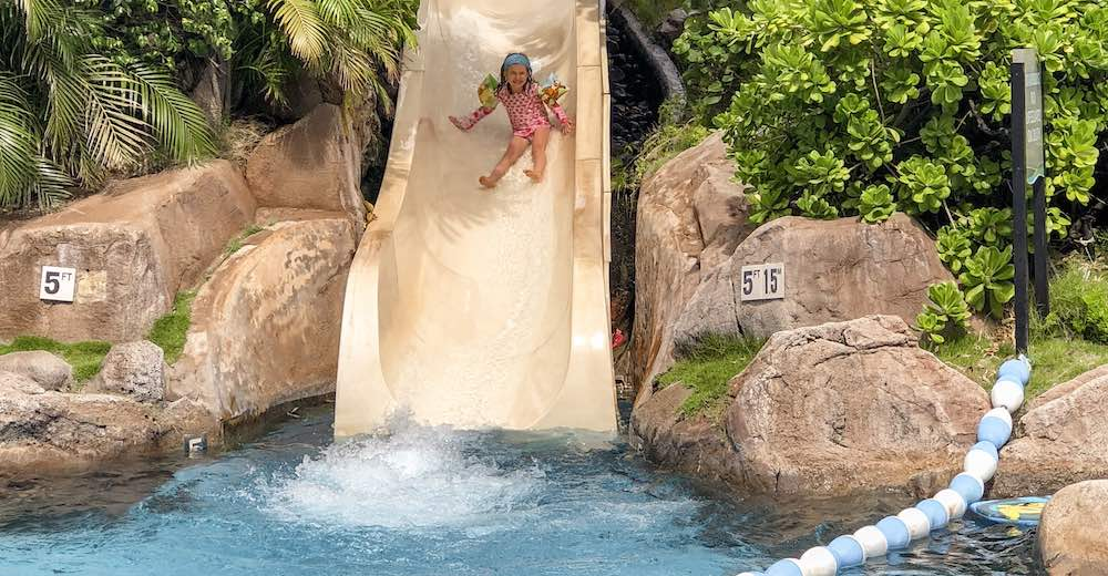 Girl sliding down the pool slide in the Westin Maui Resort and Spa, one of the best Maui places to stay