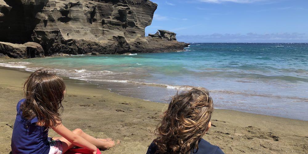 Two little girls enjoying green sands beach Big Island Hawaii