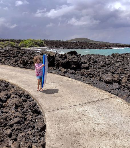 Little girl following the path to Kika'au Point beach amidst black lava rocks