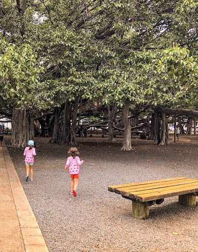 Two girls running towards the banyan tree in Maui's former whaling village of Lahaina