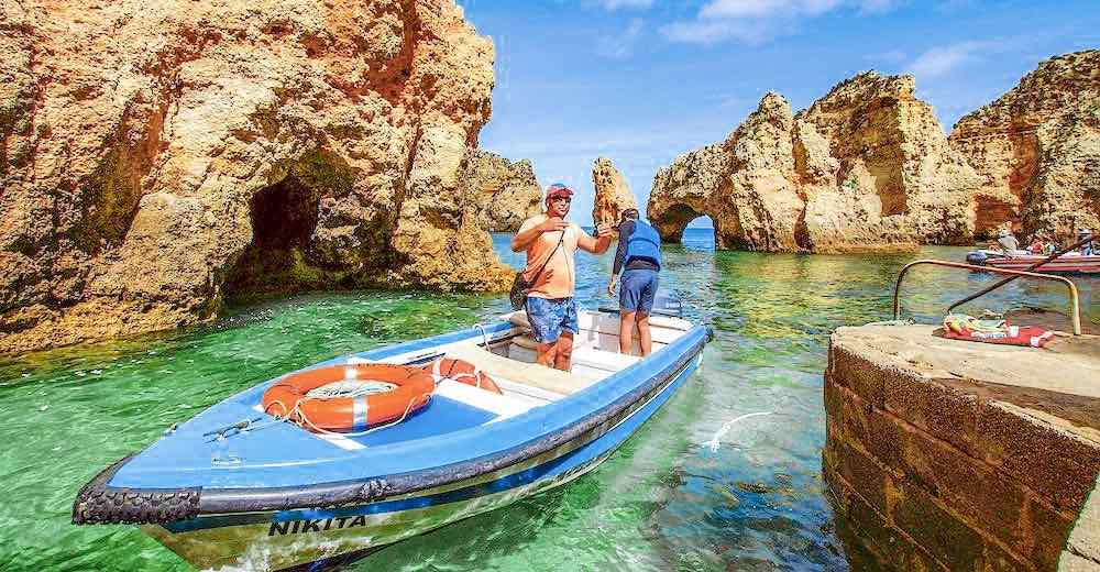 Two men on a fishing boat near Carvoeiro to see the Algarve Portugal cave and rock formations