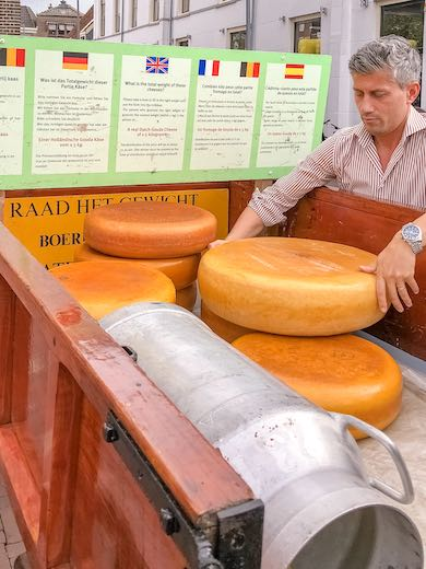 Man estimating the weight of the cheese at the Gouda cheese market in The Netherlands