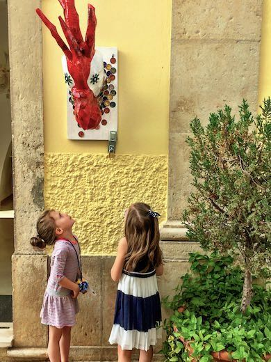 Two girls looking at a statue of a rooster in the streets of Loule near Faro Algarve