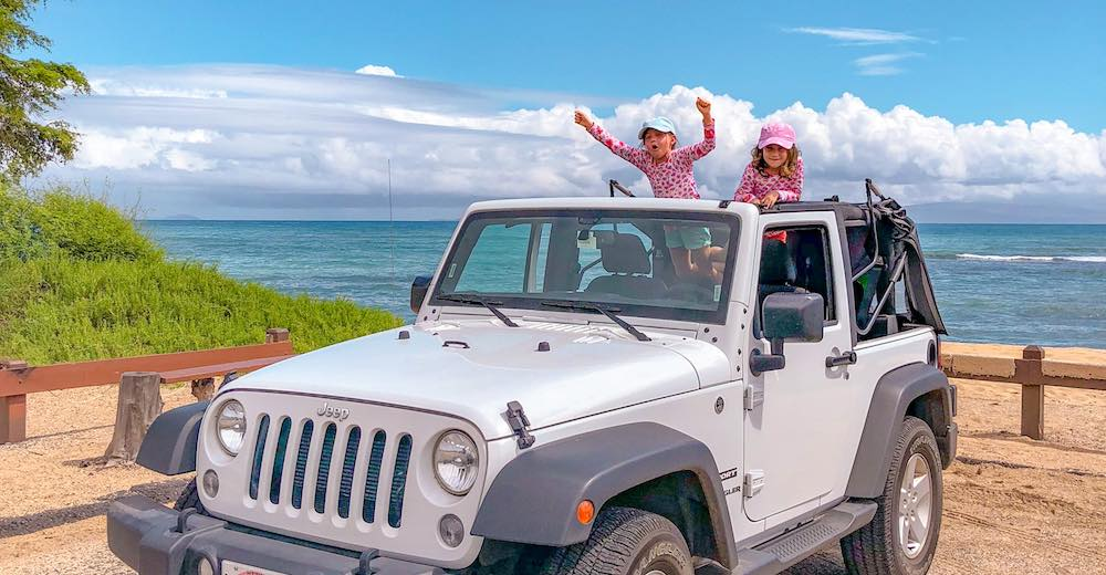 Two girls in rental car during island hopping in Hawaii vacation, learn how to travel between Hawaiian islands