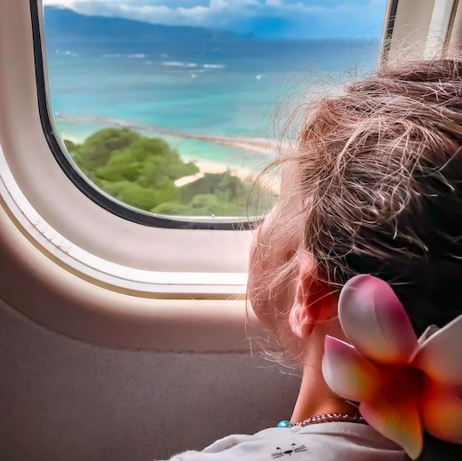 Little girl with Hawaiian flower pin in plain dreaming about which Hawaii islands to visit during your island hopping in Hawaii