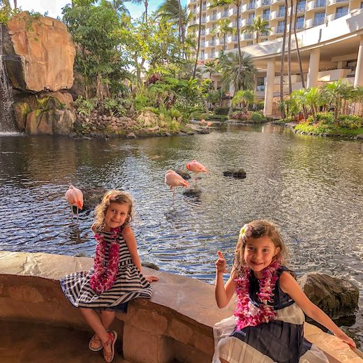 Two girls at the lobby of Westin Maui Resort with its residential flamingos
