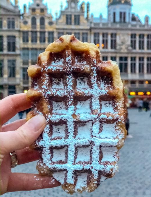 Hand holding the oval Liege waffle in Brussels to show the difference between the Liege waffles vs Brussels waffles from Belgium