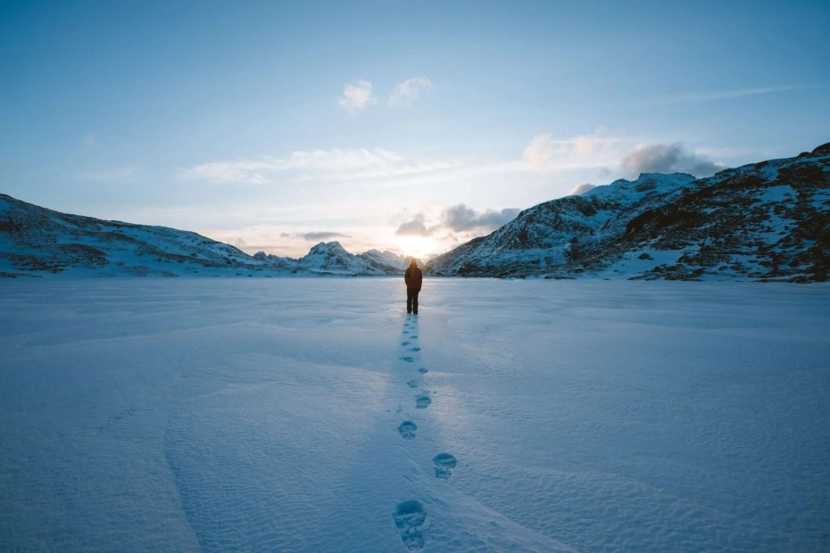 Man walking in the snow towards the sun.