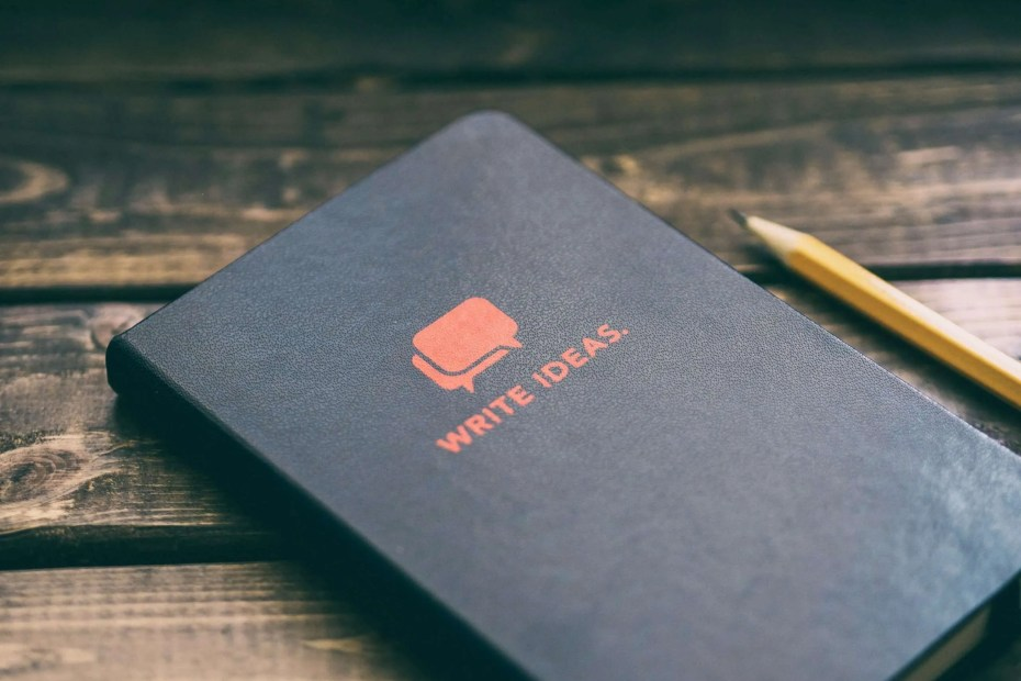 """A black notebook with the """"write ideas"""" words wrote on it. This is the creative's best tool, the idea journal."""