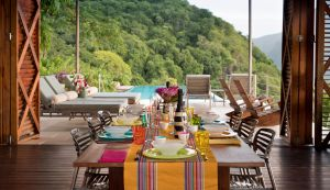 A celebratory dining table laid with colourful crockery and glasses at Cosmos St Lucia, with a view of the sun terrace and pool in the background