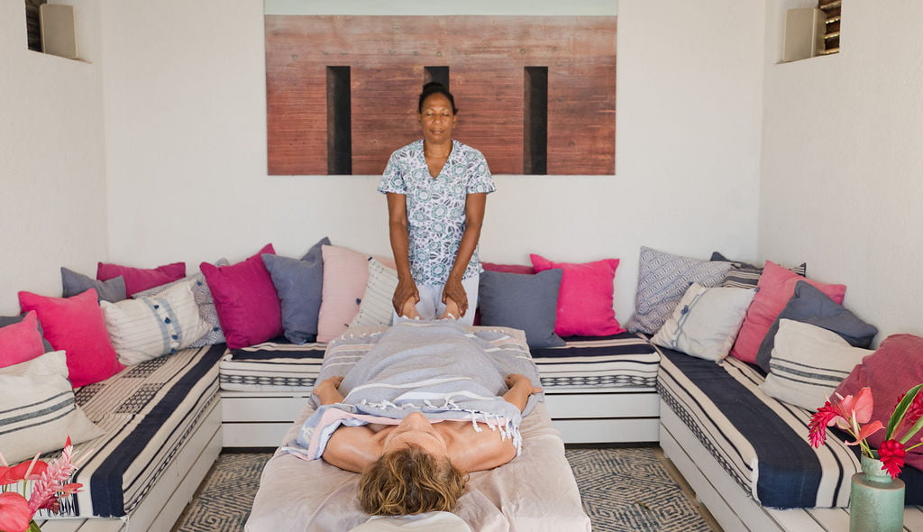 A spa therapist gives a foot massage to a woman lying on a massage table