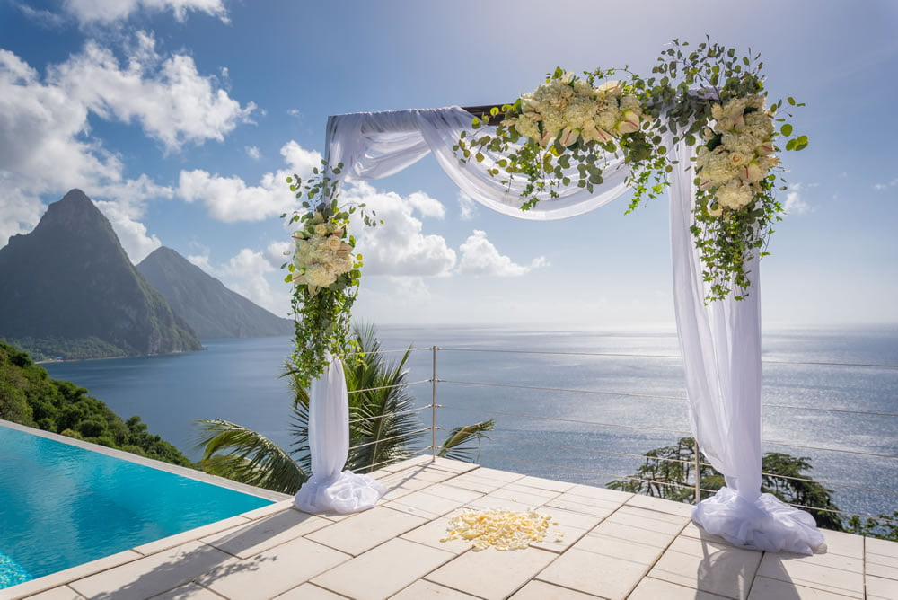 A floral arch stands on a sun terrace, with a view of the Pitons behind