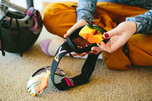 Snowboarder replacing goggle lens
