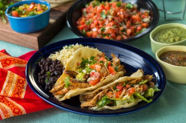 Costa Vida chicken tacos surrounded by salsas and guacamole
