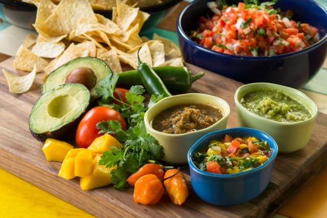 Four bowls of salsa and guacamole sit on a wooden cutting board, surrounded by diced mangos, two kinds of peppers, tomatoes, a halved avocado and tortilla chips.