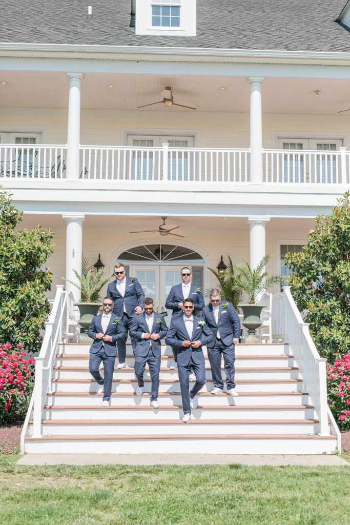 groomsmen walking down the steps at weatherly waterfront farm photography by costola photography