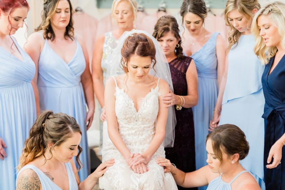 Bridesmaids praying over Bride by Costola Photography