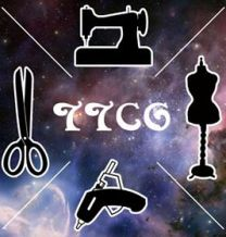 This is the logo for the TTCG. It has a vaguely Milky Way style background with TTCG in the center in a stylized font. There are various sewing implements on it as well.